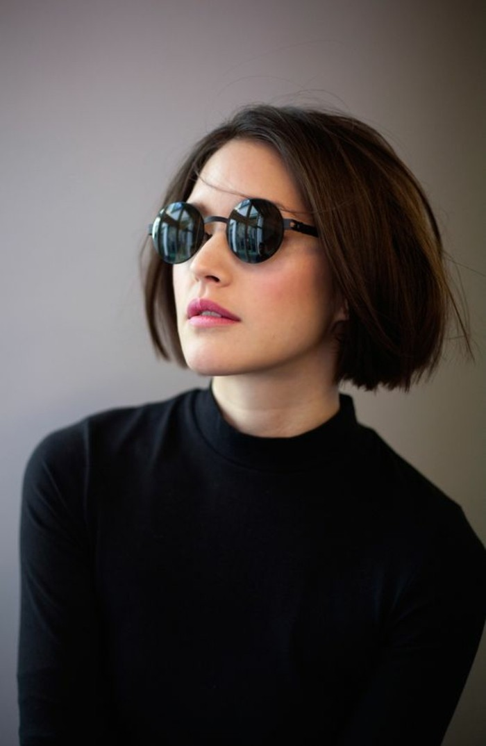 hairstyles for short hair, woman with round black glasses, and black turtleneck, with straight brown bob, parted at the side