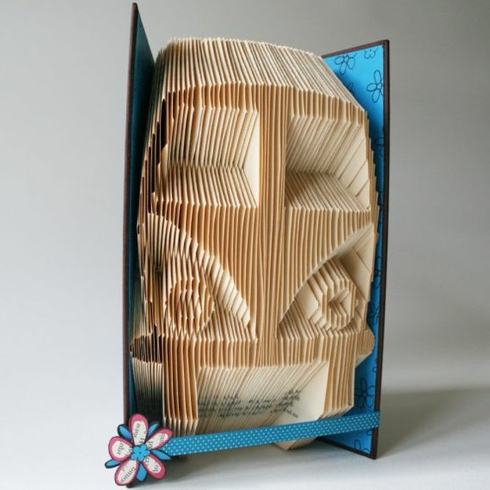 an image of a van, created from folded yellowy pages, inside an open book, with black and blue hard covers, decorated with blue ribbon with white polka dots, and a paper flower