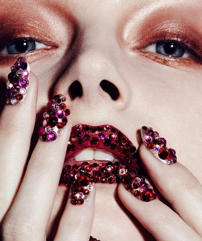 extreme close up of woman's face and fingers, brown eye make up, red lips covered with pink and purple rhinestones, fingernails covered with rhinestones in the same color