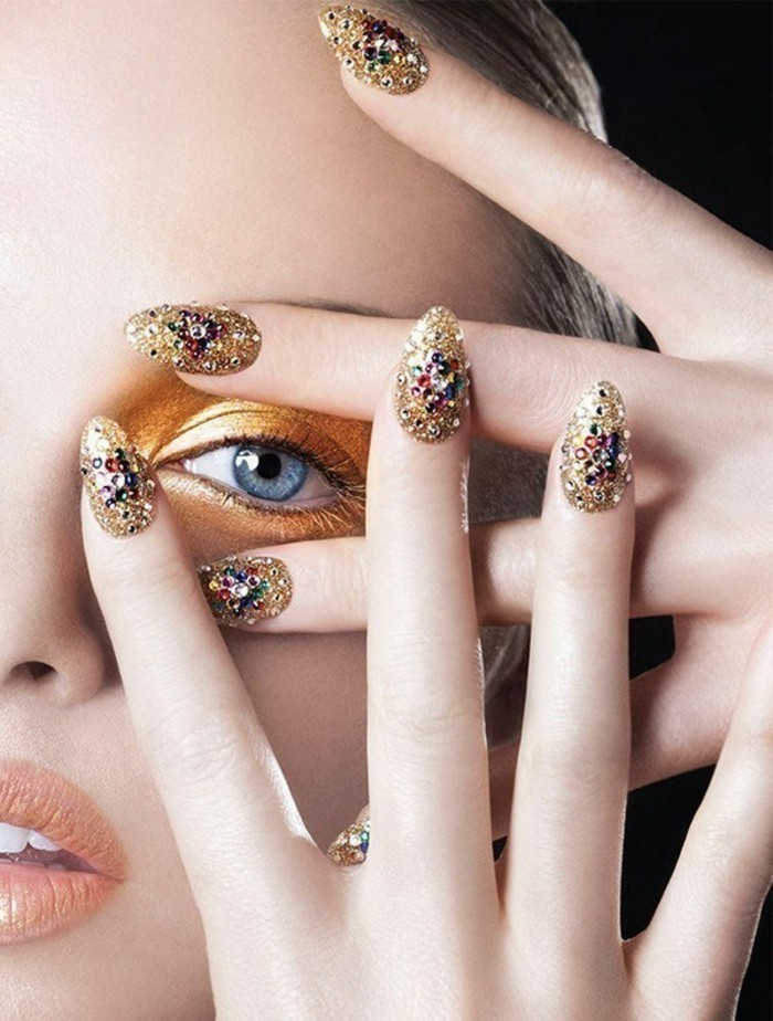 close up of woman's face and fingers, gold eye make-up and golden nails, decorated with multicolored rhinestones