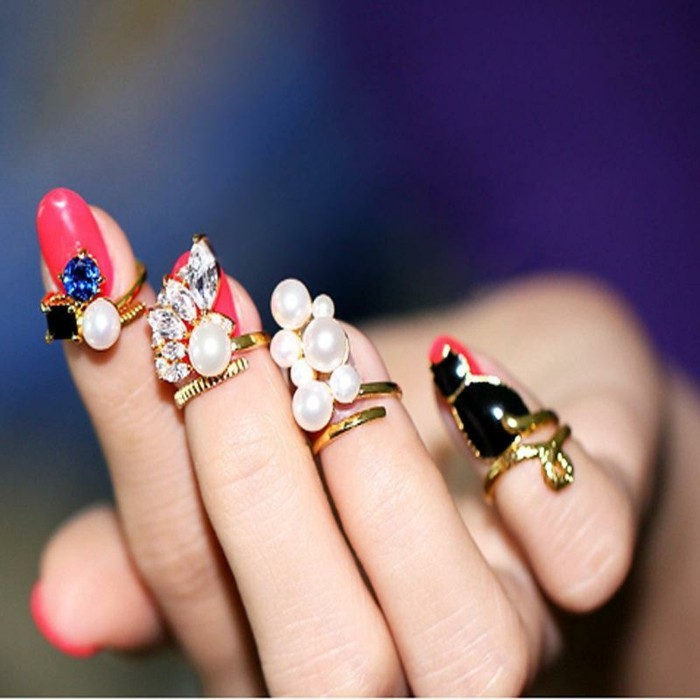 nails with rhinestones, hand with hot pink nails, small gold rings with pearls on fingertips
