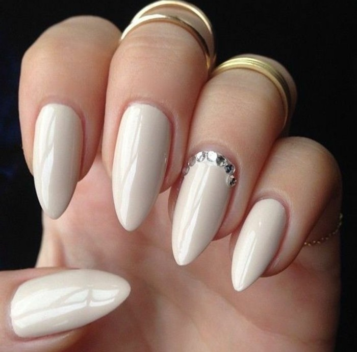 very pale nude nail-polish with rhinestone detail, on hand with several fingers