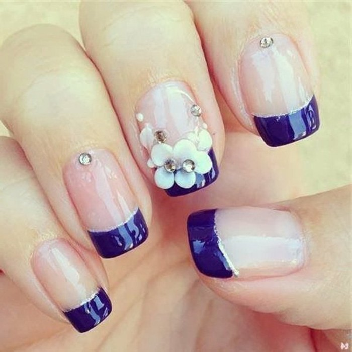 close-up of five nails, base painted in clear pale pink polish, tip painted in dark violet, acrylic flower decoration, rhinestones and silver details
