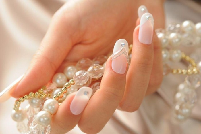 hand holding pearl necklace, pale pink nails with white tips, decorated with white dots and one rhinestone each