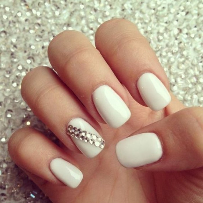 hand with white nails, one decorated with several rhinestones