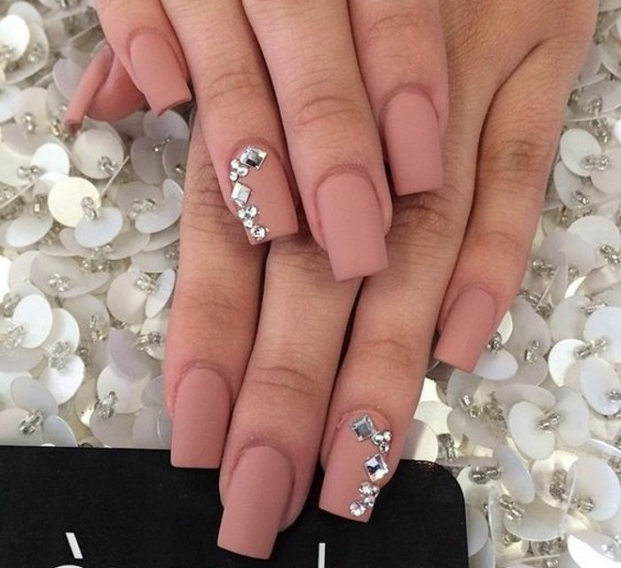 two hands with square nails, painted with dark nude matte polish, two of them decorated with round and square rhinestones