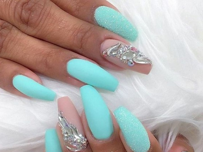 tan hands with long sharp and semi-square nails, turquoise and pink nail polish, white glitter and rhinestone decorations
