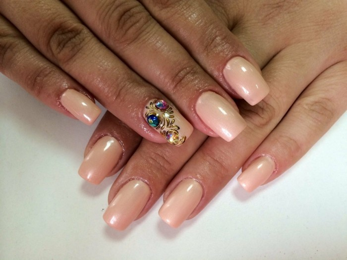 close up of two hands with nude nail-polish, only one finger decorated with three multicolored rhinestones and gold elements