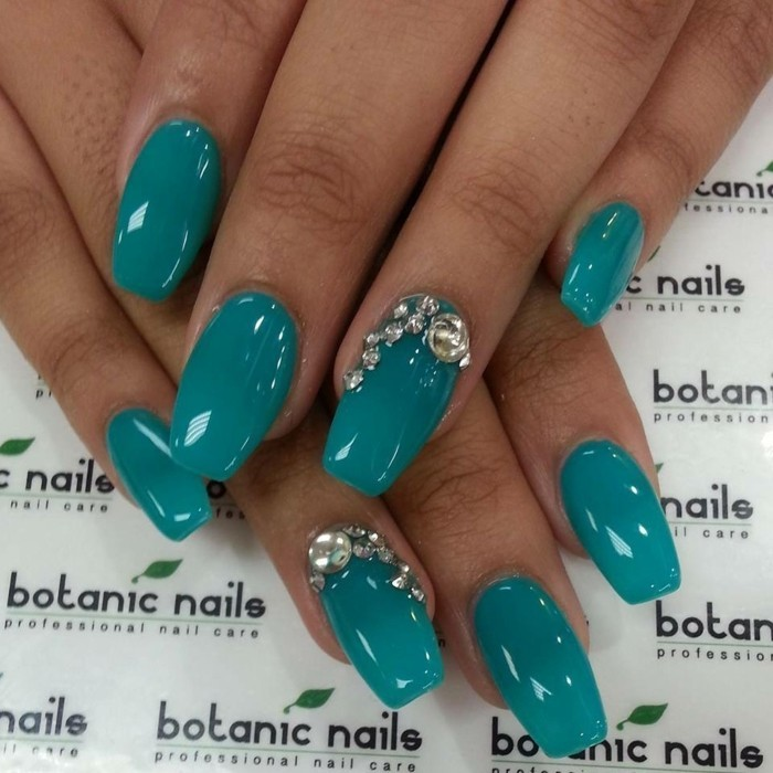 close up of tan hand with semi-square nails, painted in deep turquoise, two of the nails are decorated with silver rhinestones