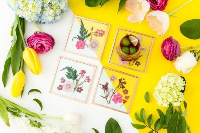best friend birthday gifts, white and yellow table, containing four glass coasters with pressed flowers, surrounded by fresh tulips and hydrangeas
