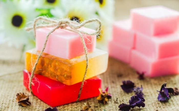 gifts for best friends, three handmade soaps in red, orange and pink, tied with a simple string, flower petals and more pink soaps in background