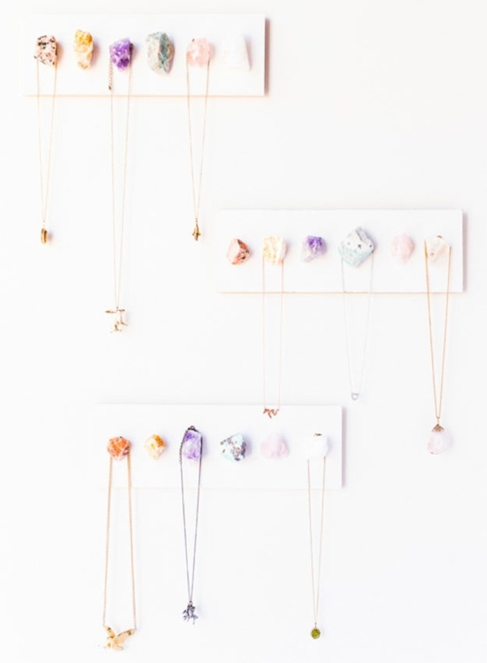 diy gifts for friends, three necklace holders, made from white wooden boards, decorated with colorful stones, several necklaces hanging from the stones