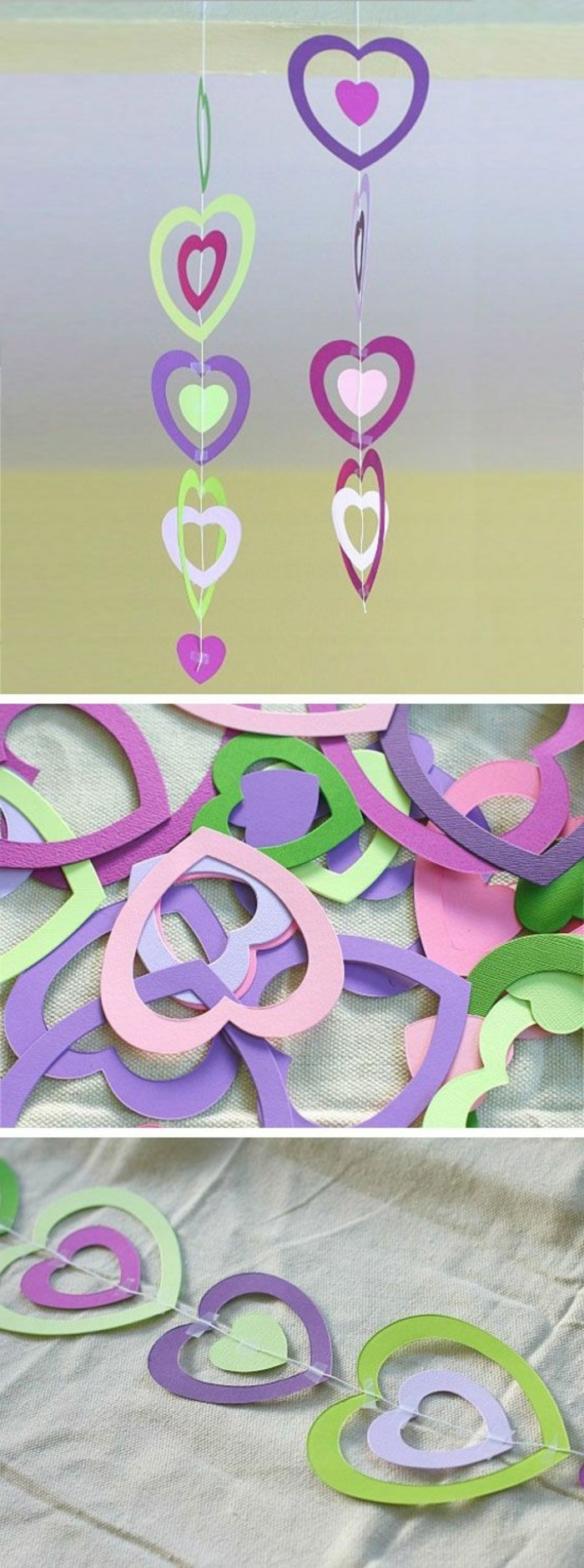 two garlands made from paper hearts, in different shades of pink, green and violet, attached together with white string and tape, close up of the garlands