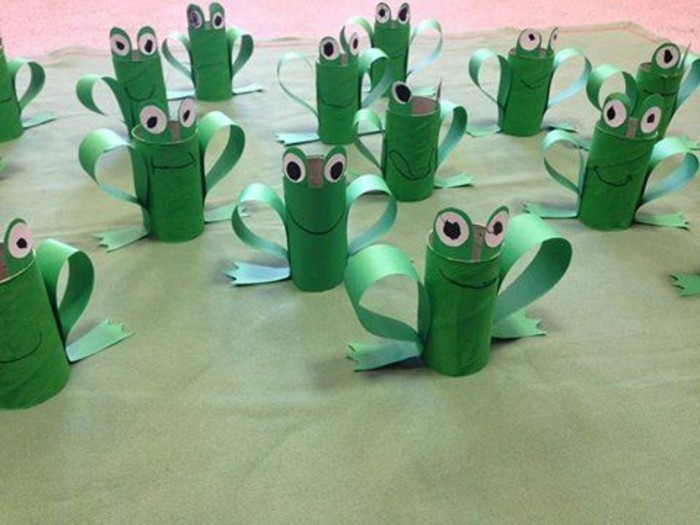 many green frogs, made from hand-painted toilet rolls, decorated with green, white and black paper cutouts