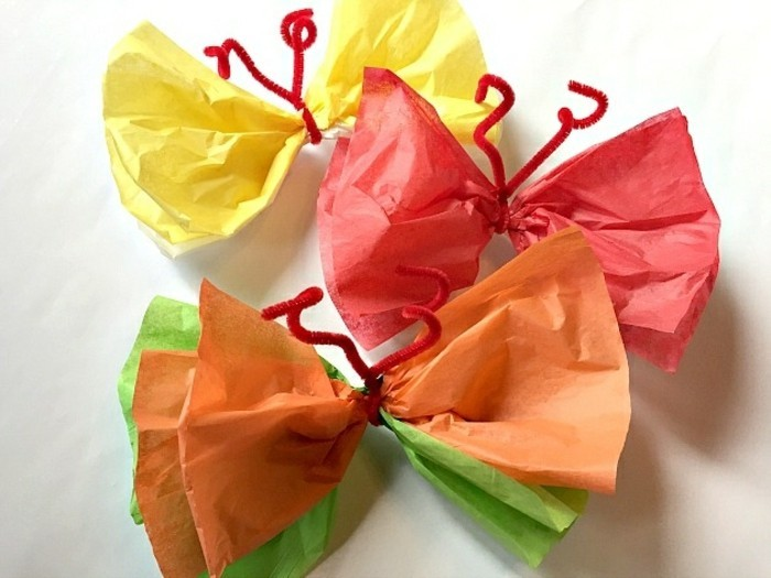 diy art projects, three butterflies made from crepe paper, in yellow and red, orange and green, tied with simple red fuzzy wire
