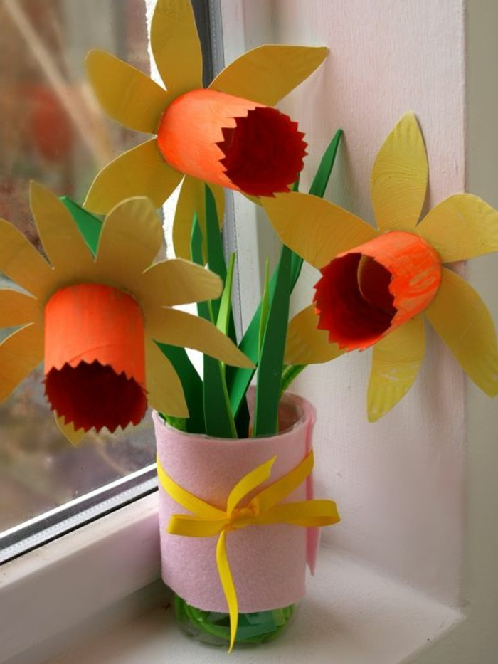 diy projects for kids, three yellow and orange daffodils, made from cardboard, with green stalks and leaves, tied together with pink felt and a yellow ribbon