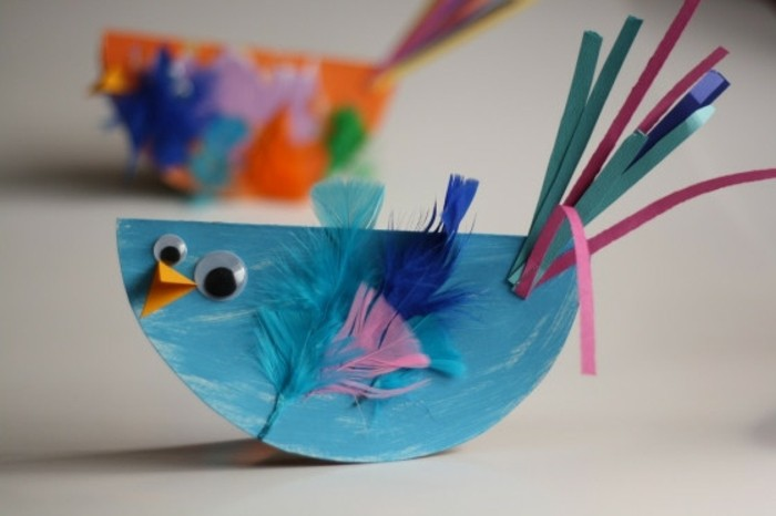 diy art projects, small handprinted blue bird, made of paper, decorated with blue and pink feathers, paper strips and googly eyes