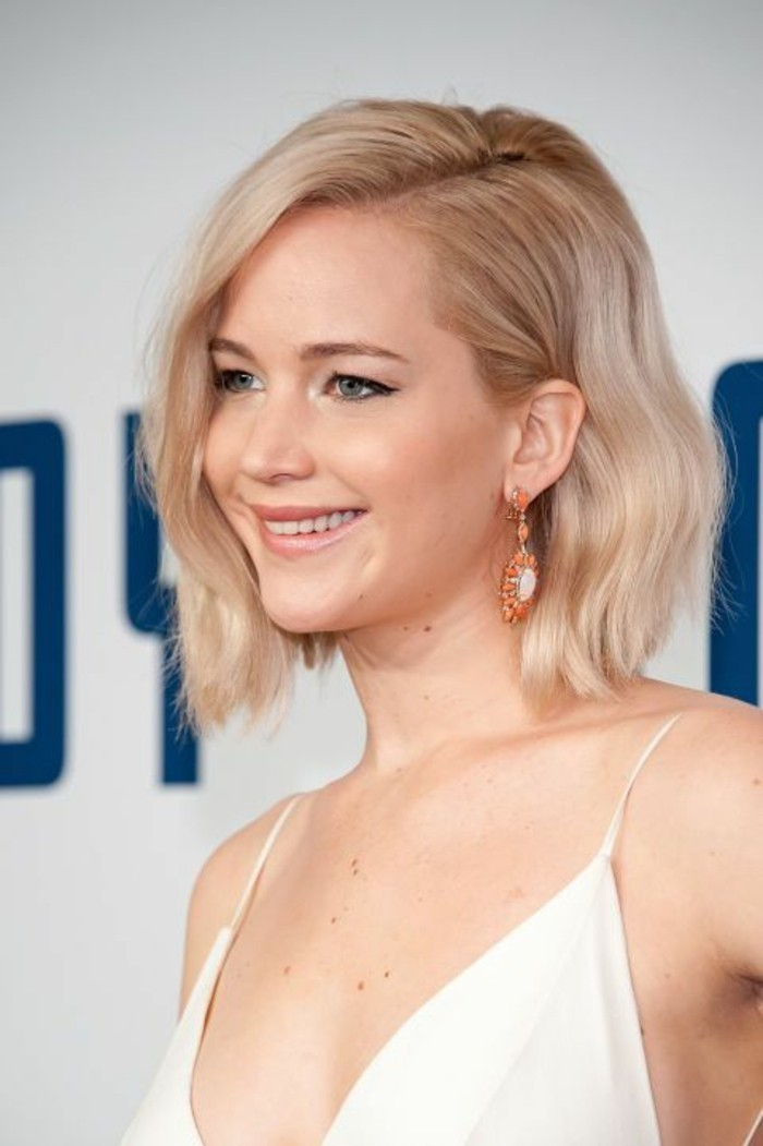 close up of jennifer lawrence, with wavy light blonde side parted bob, wearing white strappy top and orange earrings
