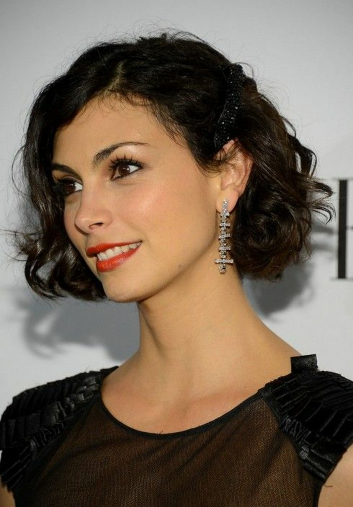 close up of morena baccarin, with curly dark brown, side parted bob, wearing red lipstick and a black top