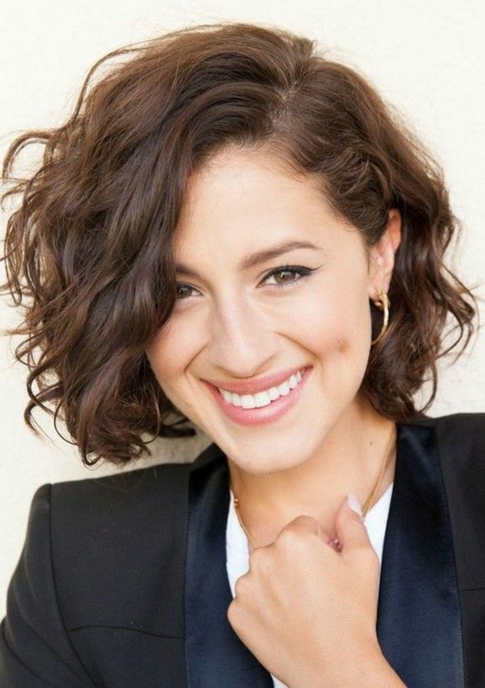 cute short haircuts, close up of a smiling woman, with curly side-parted short brown hair, bangs falling over one eye