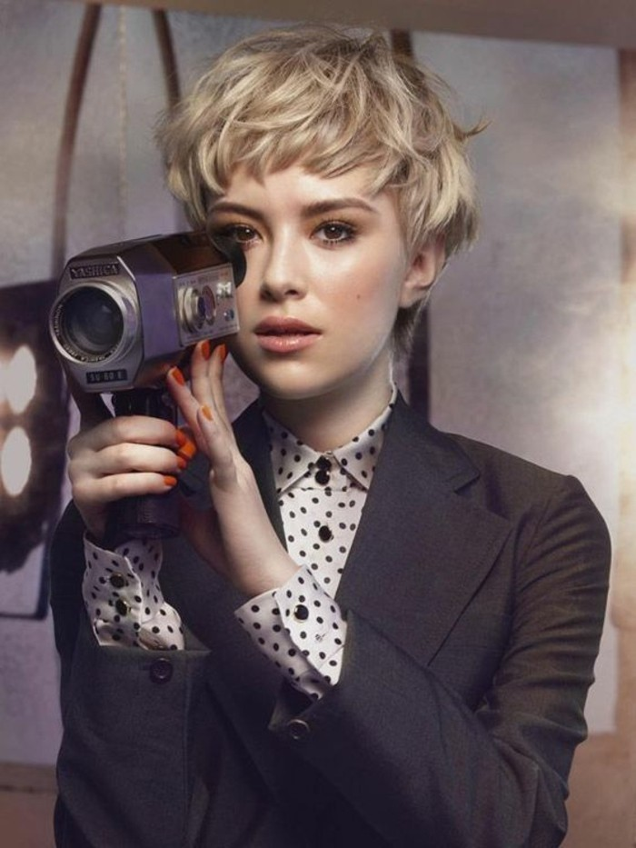 pixie cut, woman with very short, tousled and layered blonde hair, wearing a shirt and blazer, and holding a retro camera