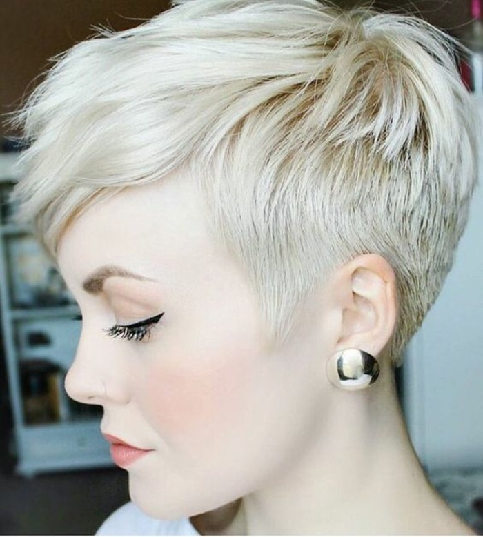 short haircuts, platinum blonde woman in profile, with hair cut short on the sides and long bangs, black eyeliner and big golden earrings
