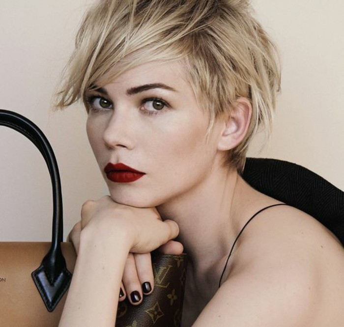 pixie cut, michele williams with short, side-swept blond hair, wearing bright red lipstick, and black nail polish