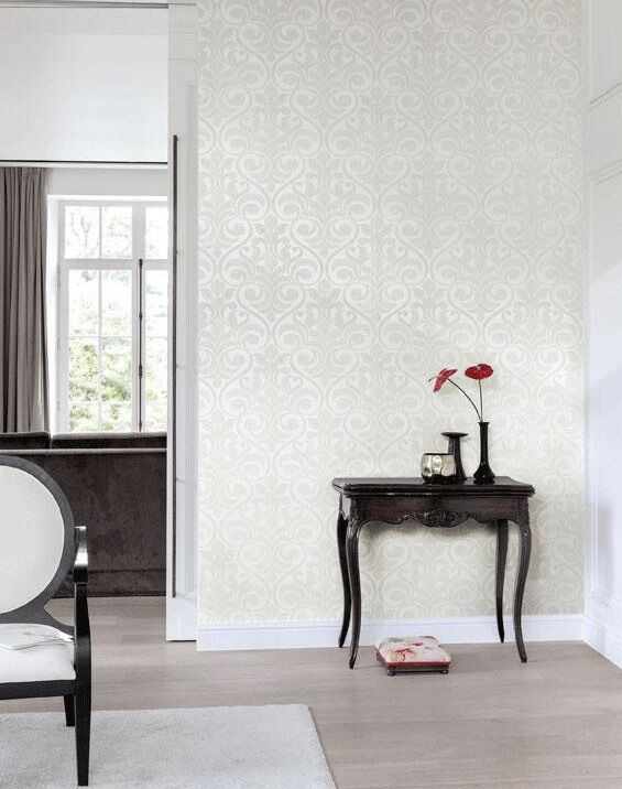 Victorian-style wallpaper in white and cream, on the wall of a white room, with vintage furniture