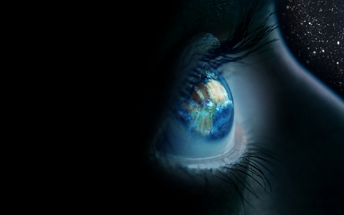 different colored eyes, close up to blue human eye, the planet earth is reflected inside, shadows and a black background with stars
