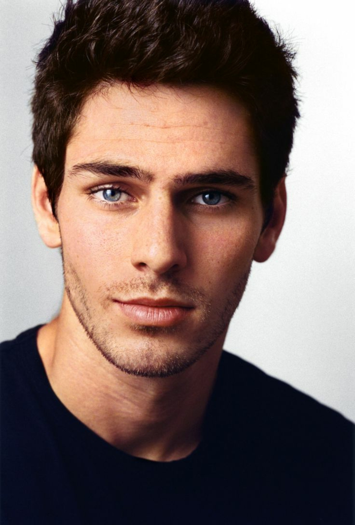 dark blue eyes, close up of a smiling young man with short dark wavy hair, with stubble and black t-shirt