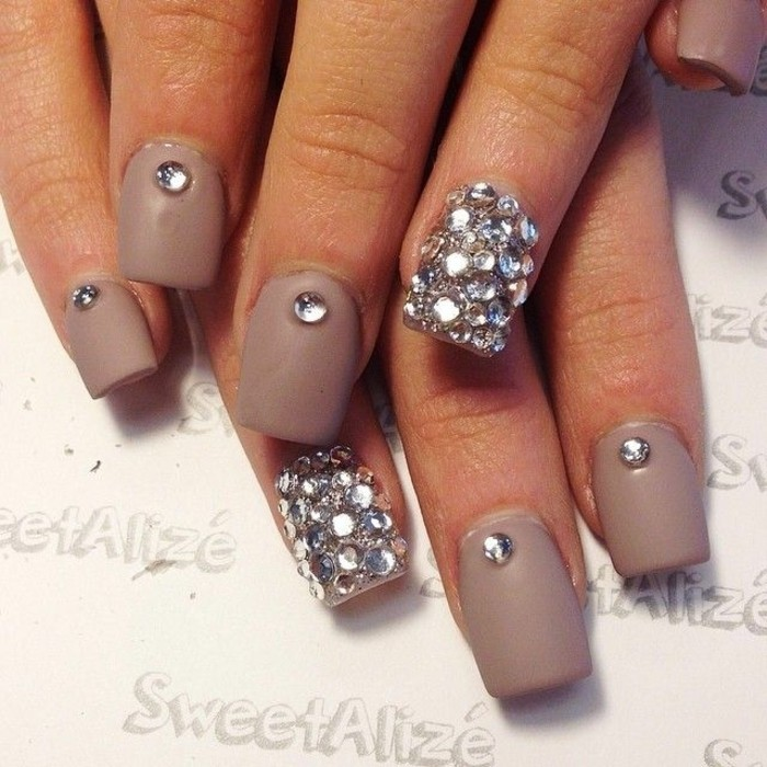bling nail designs, dark nude nails, each decorated with a single rhinestone, ring fingers' nails fully covered in rhinestones