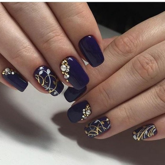 two hands with violet nail polish, several nails decorated with gold and silver drawings, rhinestones and pearls