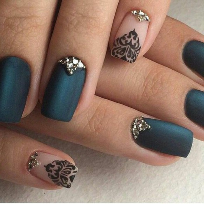 extreme close-up of two hands, five dark blue-green nails decorated with rhinestones, two clear nails with rhinestones and black drawings