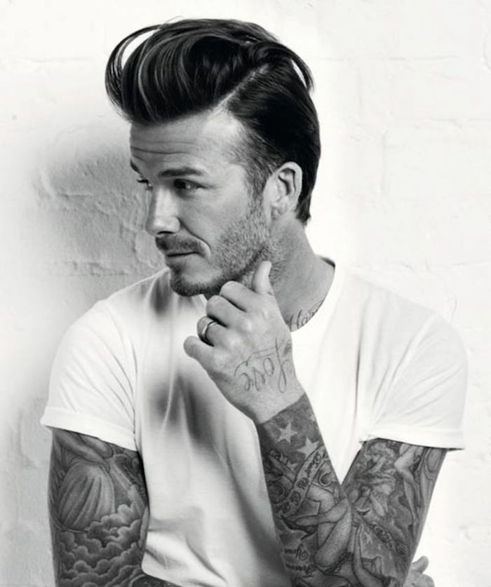 David Beckham wearing white t-shirt, with arm tattoos and stubble beard, hair with undercut and pompadour