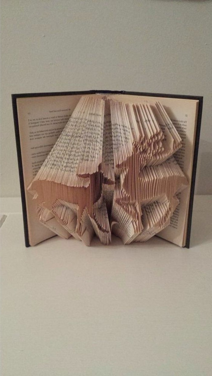 deer and elk shapes, made from folded pages, inside a vintage book, with yellowy pages, and black hard covers