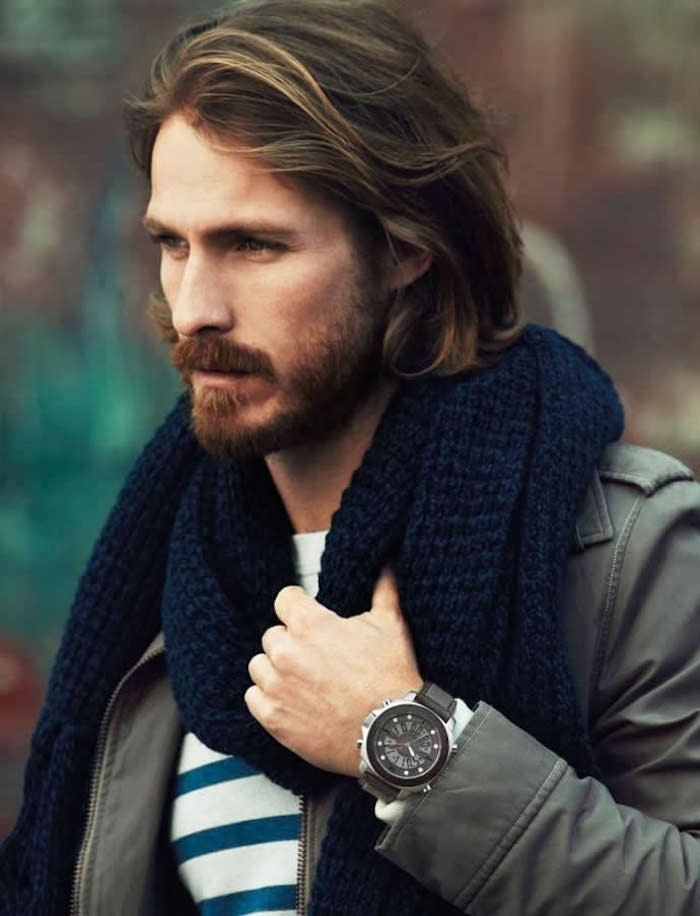 shoulder length hair, dirty blonde man with beard and mustache, wearing khaki jacket and blue chunky knit scarf