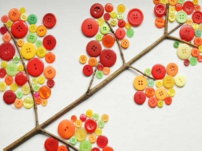 cool things to make at home, collage made from a twig stuck on white paper, decorated with multicolored buttons in different sizes, looking like autumn leaves