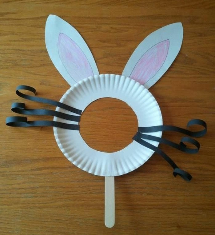 easy kids crafts, bunny mask made from white paper plate with face hole, decorated with black paper whiskers, and white hand-decorated paper ears