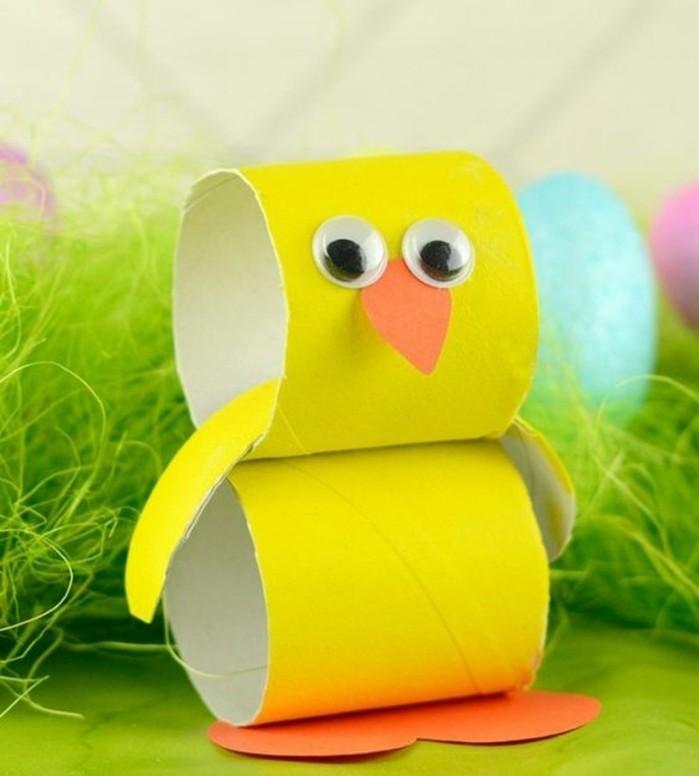 craft ideas for kids, chicken ornament made from yellow toilet paper roll, decorated with orange paper cutouts and stick-on eyes