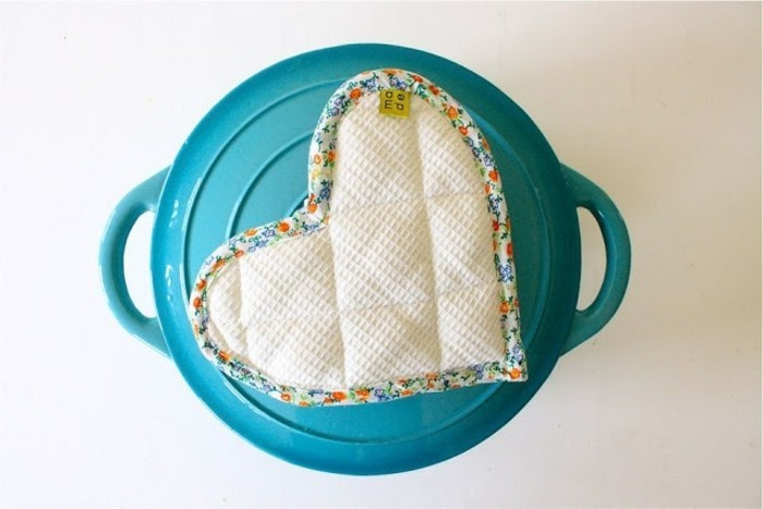diy gifts for friends, handmade pot holder shaped like a heart, made from white fabric with floral trim, placed on a turquoise pot with handles
