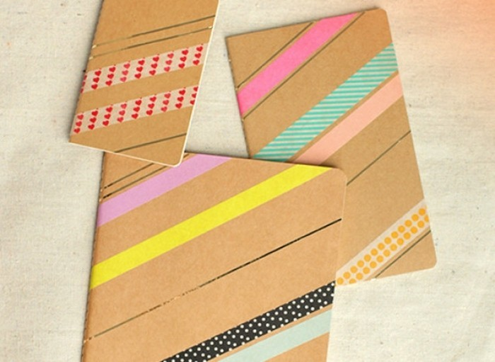 diy gifts for friends, three journals in different sizes, with cardboard covers, decorated with colorful, patterned masking tape and golden lines