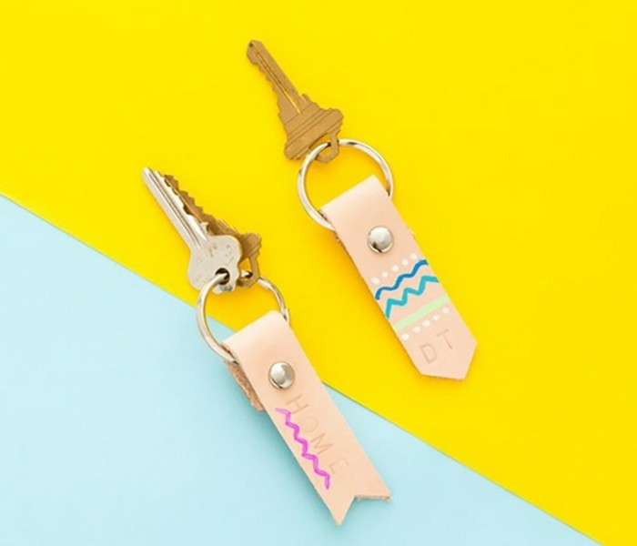 diy gifts for friends, two sets of keys, with handmade leather keyrings, in pale pink and decorated with gold studs, and pink and blue scribbles