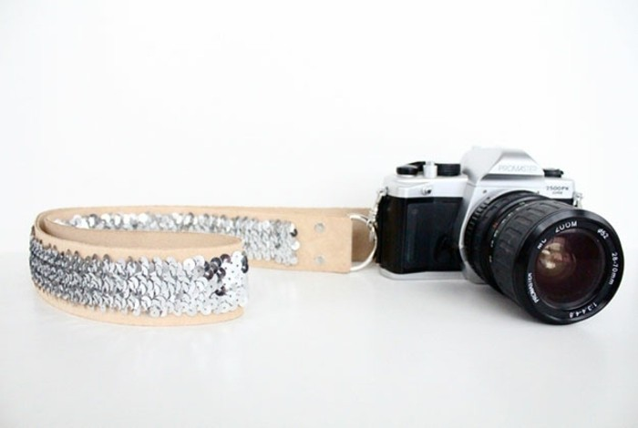 diy gifts for friends, black and silver retro camera, attached to a cream colored leather neck strap, hand-decorated with silver sequins