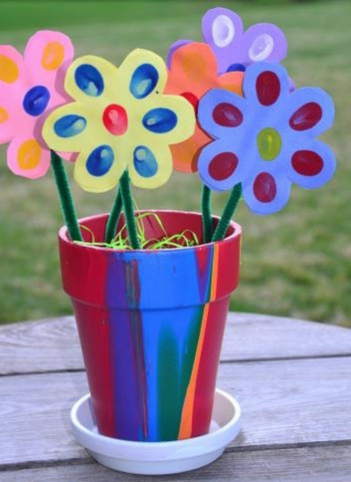 hand-painted clay flower pot, containing five paper flowers in different colors, decorated with finger prints, and attached to green fuzzy wire
