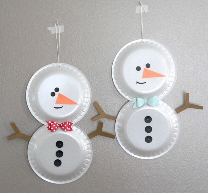 diys for your room, two snowmen made from two paper plates stuck together, decorated with paper cutouts, black buttons and colorful bowties