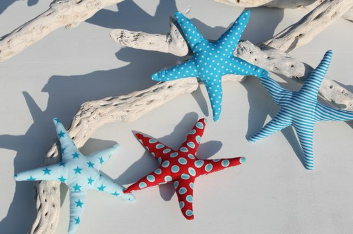 summer craft ideas, four stuffed starfish, made from blue and red patterned fabric, placed over white-painted driftwood