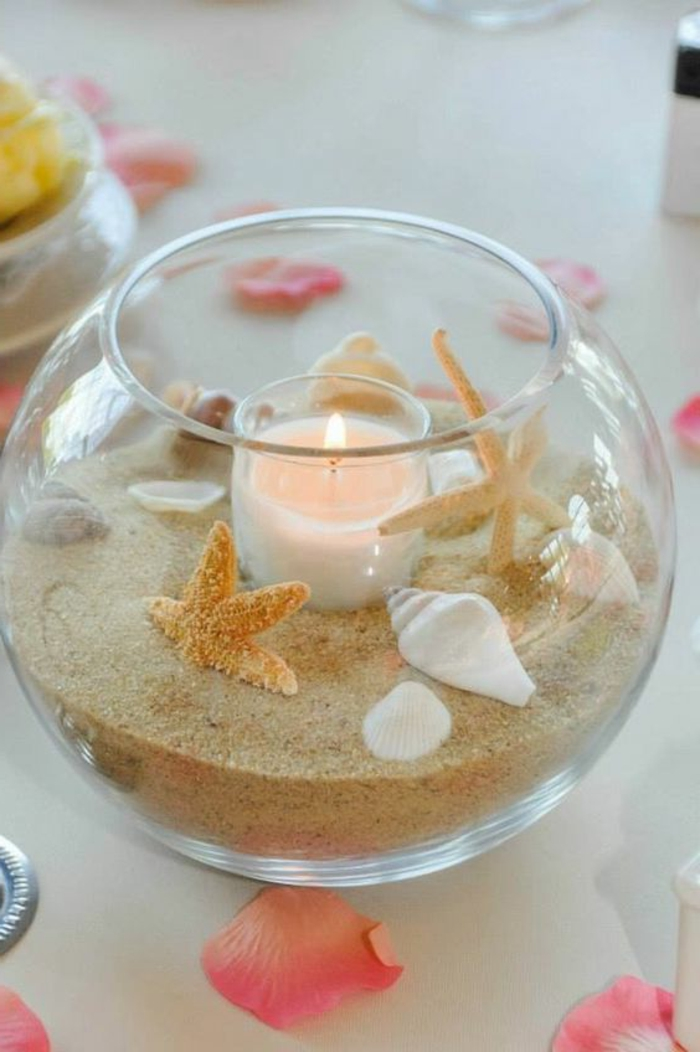 summer crafts for adults, round glass bowl, half-filled with sand, various seashells and dried starfish, containing one lit candle in glass holder