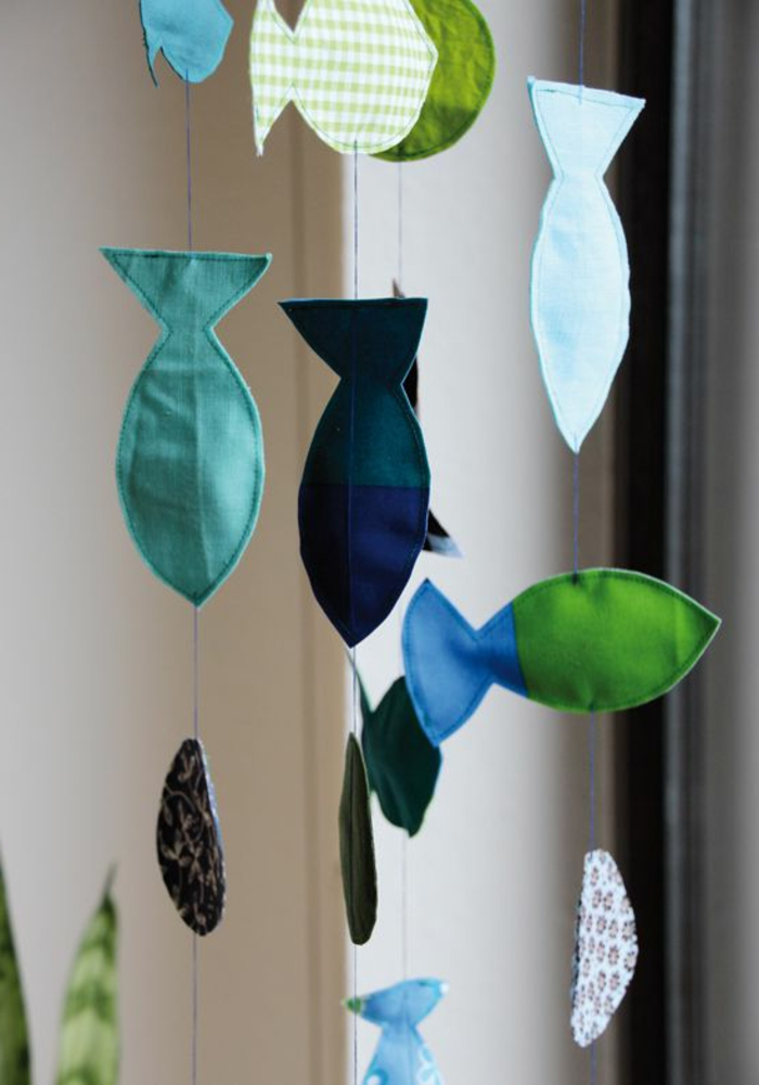 easy fun diys, four garlands made from little fabric fish, in different shades of blue and green, hanging from blue pieces of thread