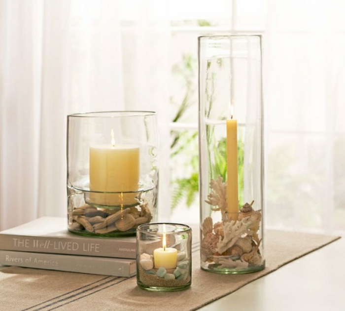 summer craft ideas, three glass containers in different shapes and sizes, containing either pebbles, small pieces of driftwood or corals, and a lit candle
