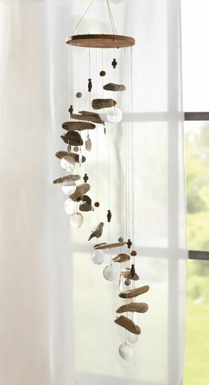 summer crafts for adults, wind chime made from small, asymmetrical pieces of driftwood, tied to a wooden circle, with string decorated with small, flat and round glass ornaments